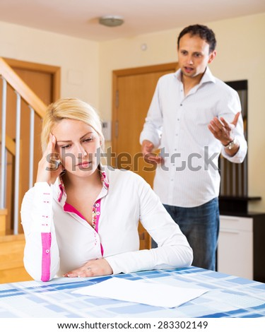 Family quarrel. Sad husband and wife during quarrel  in living room - stock photo