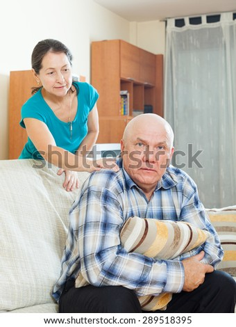 Family quarrel. Upset senior man with sad wife at home