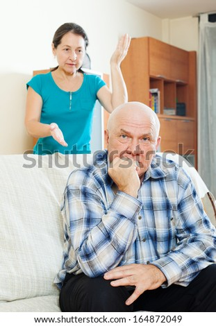 Family quarrel with a wife arguing with an upset mature man. - stock photo