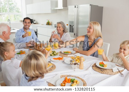 Family raising their glasses together before eating