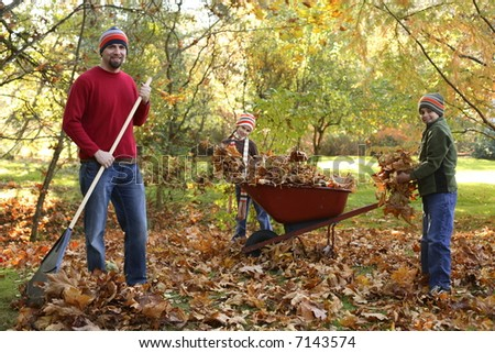 Family raking leaves - stock photo