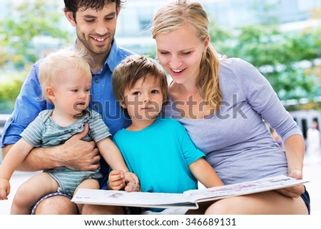 Family reading book - stock photo