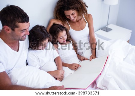 Family reading book together on bed in bedroom