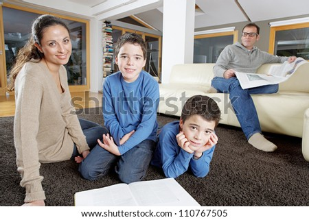 Family reading in living room on Sunday, looking at the camera and smiling. - stock photo