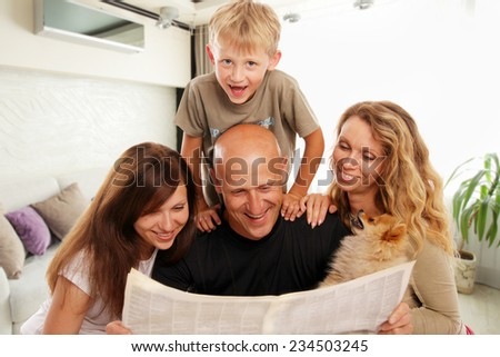 Family reads the newspaper at home - stock photo