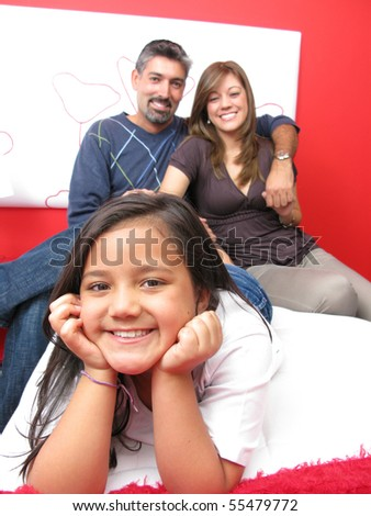 Family reclining in bed smiling at camera - stock photo