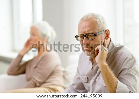 family, relations, age and people concept - senior couple sitting on sofa at home - stock photo