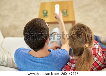 family, relations and leisure concept - close up of couple with remote control watching tv together at home - stock photo