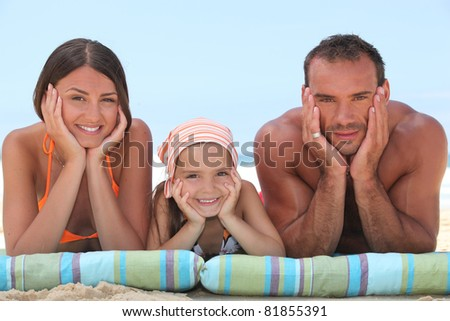 Family relaxing at the beach - stock photo