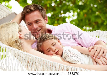 Family Relaxing In Beach Hammock With Sleeping Daughter - stock photo