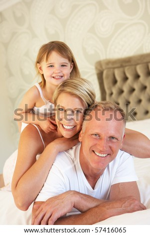Family Relaxing In Bedroom - stock photo