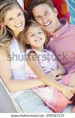 Family Relaxing In Garden Hammock Together - stock photo