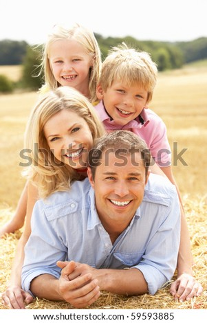 Family Relaxing In Summer Harvested Field - stock photo