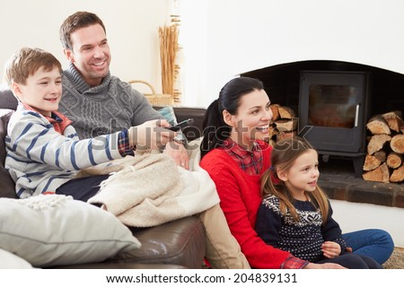 Family Relaxing Indoors Watching Television Together - stock photo