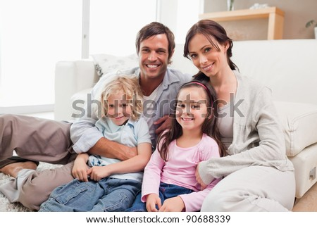 Family relaxing on a sofa in a living room - stock photo