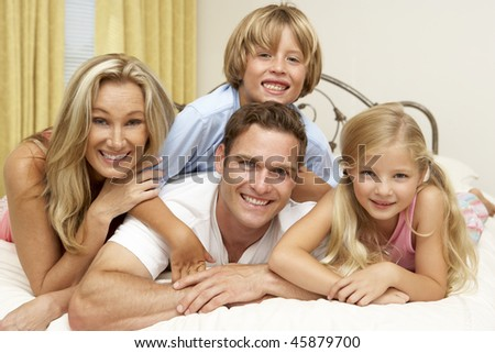 Family Relaxing On Bed At Home - stock photo
