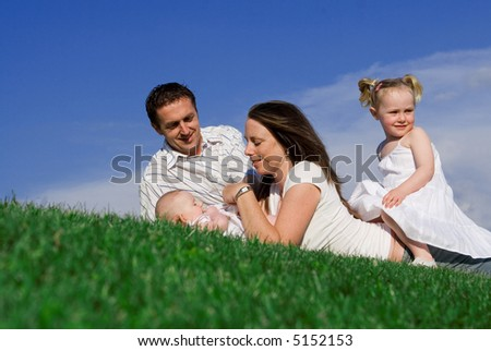 family relaxing on grassy slope - stock photo