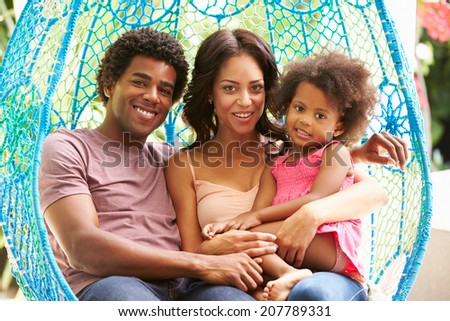 Family Relaxing On Outdoor Garden Swing Seat - stock photo