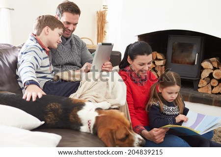 Family Relaxing Reading Book And Using Digital Tablet - stock photo