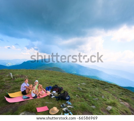 Family resting on a summer mountain top and thunderstorm in the distance (Goverla Mount, Ukraine) - stock photo