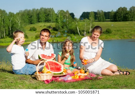 family resting on the lake