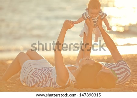 Family resting on the sea during sunset - stock photo