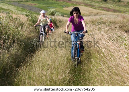 Family riding a bicycles on the countryside in summer time - stock photo