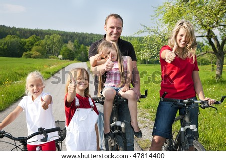 Family riding bicycles in spring - stock photo