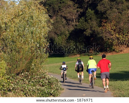 Family riding bikes in a park - stock photo