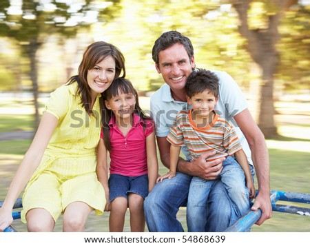 Family Riding On Roundabout In Park - stock photo