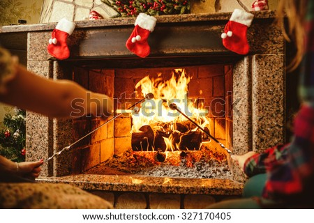 Family roasting marshmallows by the fire. Cozy chalet home with fireplace decorated with traditional Christmas ornaments. Cozy relaxed magical atmosphere in a chalet. Holiday concept. - stock photo