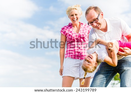 Family romping on field with parents carrying child - stock photo