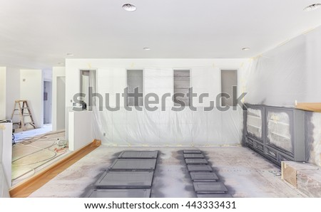 Family room draped in plastic for trim painting - stock photo
