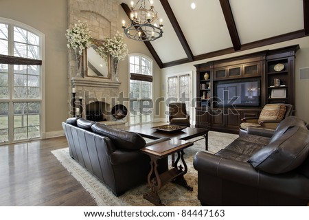 Family room in luxury home with two story stone fireplace - stock photo