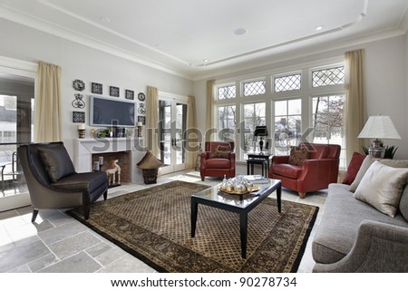 Family room in luxury home with wall of windows and fireplace - stock photo
