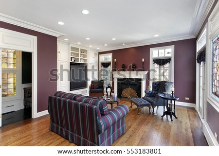 Family room in upscale home with maroon walls.