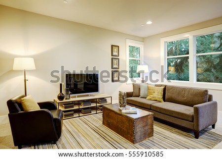 Family room interior with gray sofa facing a black leather armchair  across from a trunk coffee table atop a gray and brown striped rug.  Northwest, USA