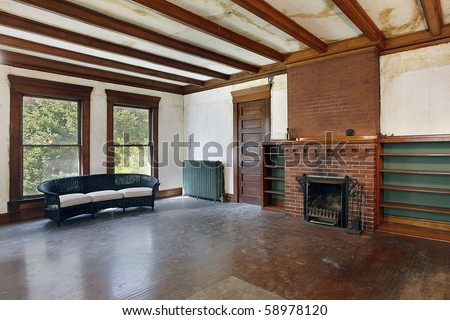 Family room with fireplace in old abandoned home - stock photo