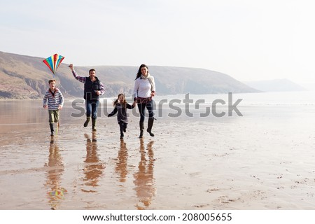 Family Running Along Winter Beach Flying Kite - stock photo