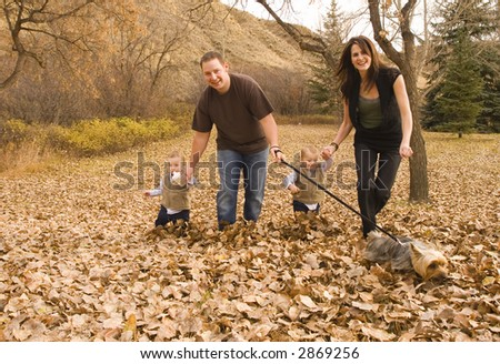family running and playing through the leaves in Autumn - stock photo