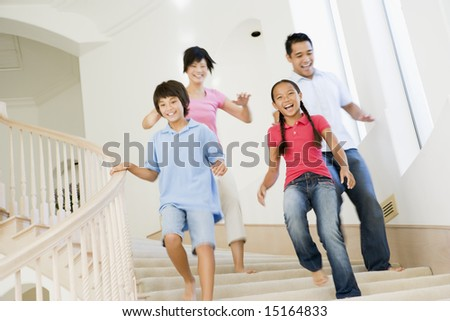 Family running down staircase smiling - stock photo