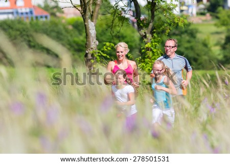 Family running for better fitness in summer through beautiful landscape - stock photo