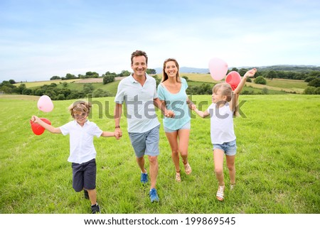 Family running in countryside, kids holding balloons - stock photo