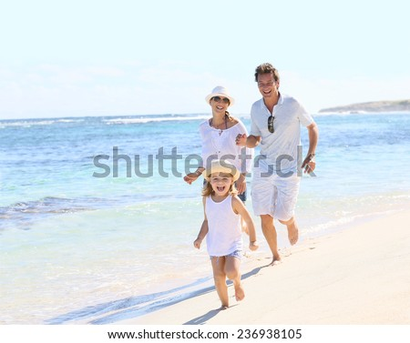Family running on a white sandy beach - stock photo