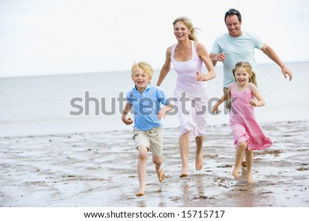 Family running on beach smiling - stock photo