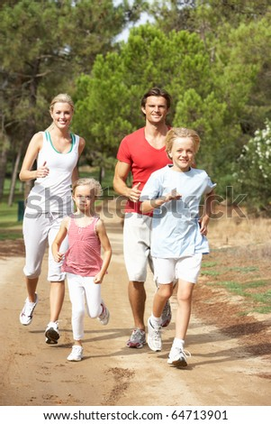 Family running on path in park - stock photo