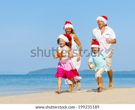Family running on the beach in Christmas. - stock photo