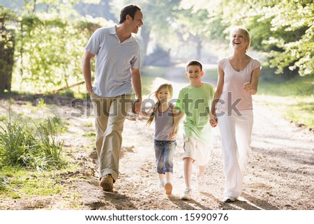 Family running outdoors holding hands and smiling - stock photo
