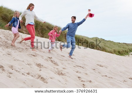 Family Running Through Sand Dunes Together - stock photo