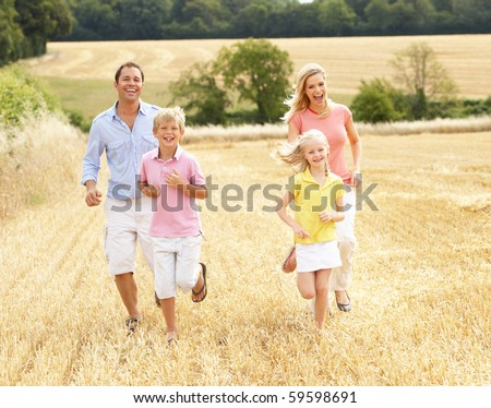 Family Running Together Through Summer Harvested Field - stock photo